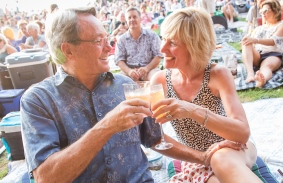 A couple raises their glasses on the Lawn