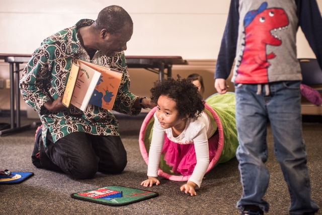 Wolf Trap Teaching Artist shows a book to a child.